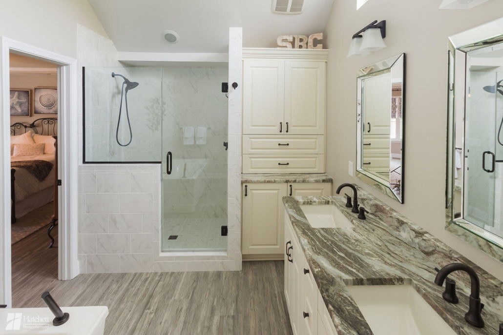 Tile shower with glass enclosure and built-in linen storage cabinet